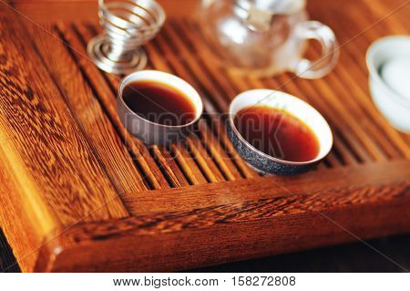 aromatic Chinese tea shu puerh, teacups on a wooden board, Chinese tea ceremony
