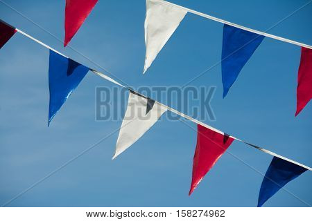 triangle flags against a blue sky background