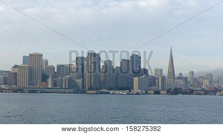The port and the financial district of San Francisco from the water, skyscraper and transamerican pyramid, cloudy sky,