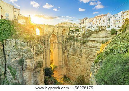 Puente Nuevo bridge colored with light of setting sun Ronda Andalusia Spain
