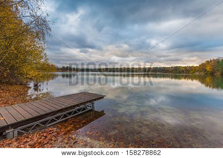 Lakeside with jetty, fallen leaves and treeline in bright autumn colors. Early morning scenic view with cloudy sky and its reflection on the water surface.
