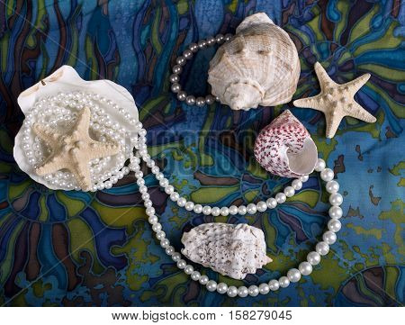 Still-life with sea cockleshells and pearls on blue background