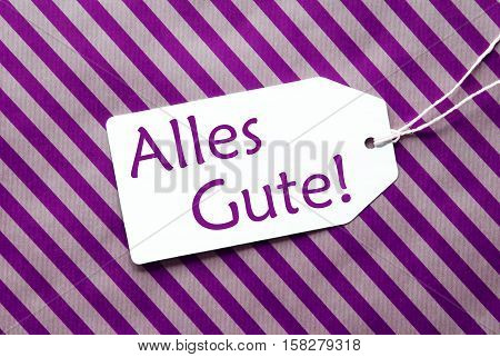 One Label On A Purple Striped Wrapping Paper. Textured Background. Tag With Ribbon. German Text Alles Gute Means Best Wishes