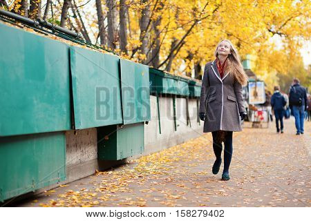 Young Woman Walking Near Bookseller Boxes In Paris