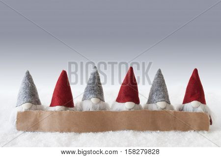 Label With Copy Space For Advertisement. Christmas Greeting Card With Gnomes. Silver Background With Snow