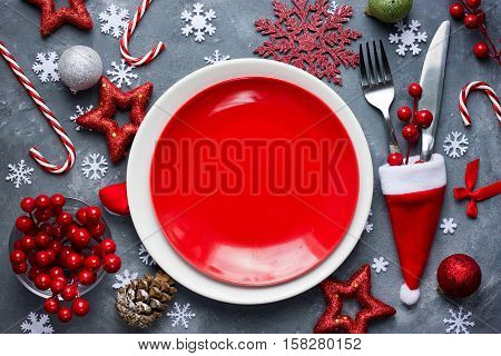 Christmas table place setting with empty red plate cutlery in santa hat with festive decorations bauble snowflake star bow ball pinecone berry candy cane. Christmas Xmas New Year holiday background