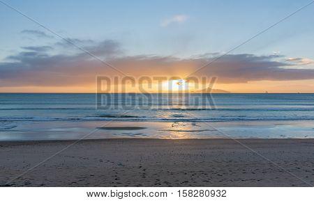 Sunrise on beach Waipu Cove sun breaking through low cloud on horizon glistening across sea