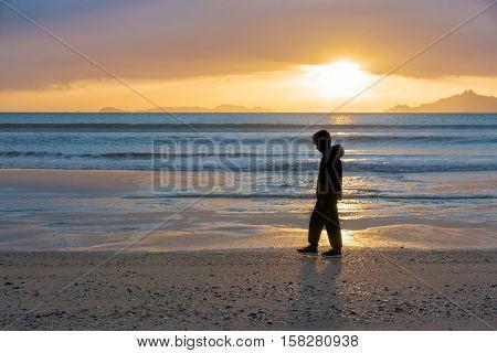 Sunrise on beach Waipu Cove as boy silhouetted walks through glow of sun across water and beach