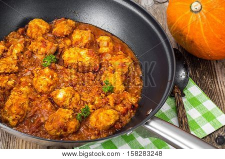 Chicken meatballs with vegetable spicy sauce in the pan. Studio Photo