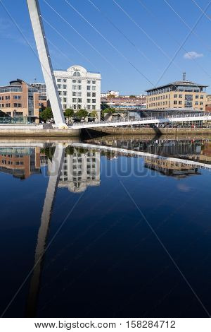 Beautiful reflection of the Gateshead Millenium Foot Bridge and Buildings in Newcastle England