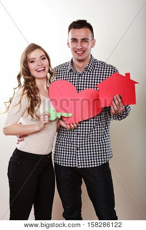 Smiling young couple holding paper house key and heart sign love symbol. Husband and wife dreaming about new home. Housing and real estate concept.