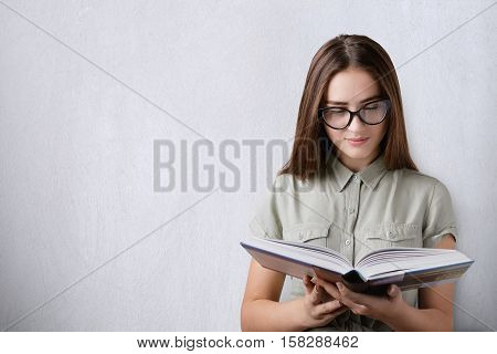 Education and studying. A portrait of a clever beautiful girl with long dark hair wearing glasses holding and reading a hardcover book on white background. An attentive reading of the book