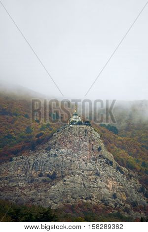 Mountain landscape. High in the mountains church temple stands on a rock. In the mountains, a cloudy autumn day. Against the background of the church of forested mountains. In the mountains of cloud or fog. pilgrimage place. Christian orthodox church, chu