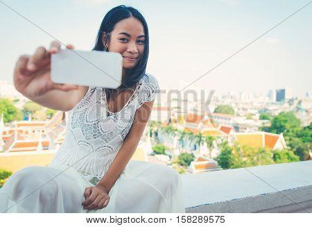 Thai woman taking selfie in Bangkok on a balcony