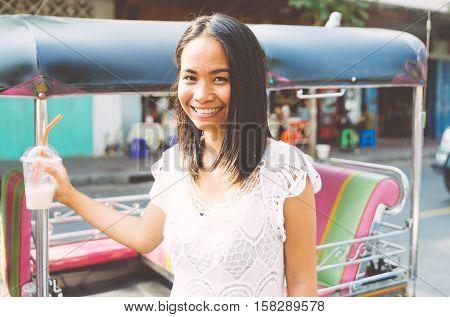 Thai woman with tuk tuk taxi in Bangkok