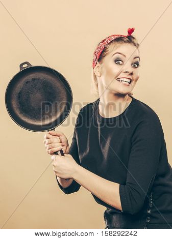 Joy and fun during food preparation. Blonde smiling woman in retro style having fun in kitchen. Playful girl with accessories of cooking.