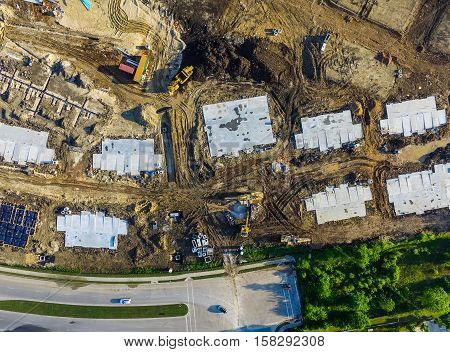 Looking straight down above construction with foundation squares and pipelines and construction vehicles Austin Texas USA aerial view wide angle