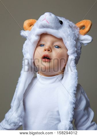 Cute adorable pretty baby with funny expression on her face making baa like a sheep wearing a sheep hat hood with yellow horns on top and white shirt on a light background New Year  concept studio