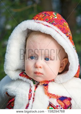 Closeup portrait of a curious cute blond baby with blue eyes in a white and red fur coat on a sunny winter day