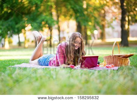 Girl Having A Picnic And Surfing In The Net