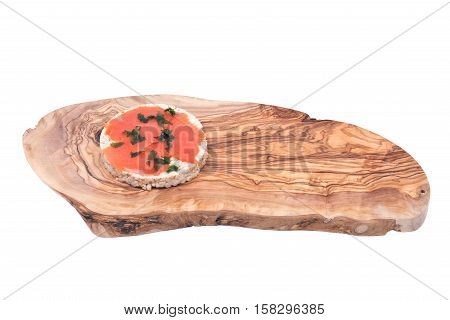 Smoked wild pacific sockeye salmon with parsley on organic brown rice cake and olive wood cutting board isolated on white background