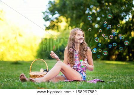 Young Girl Sitting On The Grass Blowing Bubbles