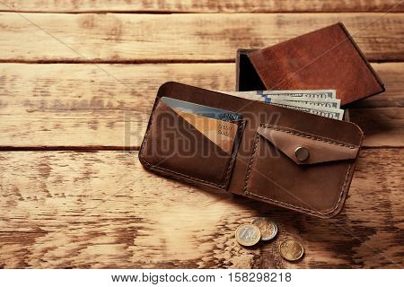 Stylish leather wallet with money and box on wooden background