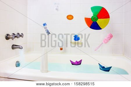 Bathroom clean home interior. Colorful child toys and accessories falling in bathtub hanging in air. Duck ball boats cream soap scrub and shampoo tubes tap water running. Health lifestyle childhood fun bathing washing concept.