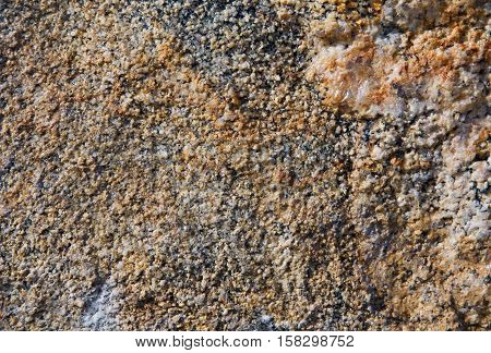 Orange yellow red stone textured granulated background closeup gross