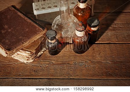 Vintage glass bottles with flask on wooden background, closeup