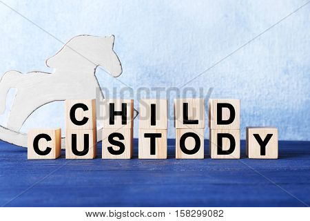 Cubes with text CHILD CUSTODY and toy on light background