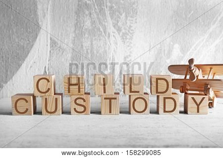 Cubes with text CHILD CUSTODY and toy plane on wall background