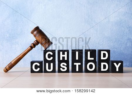 Court gavel and cubes with text CHILD CUSTODY on light background