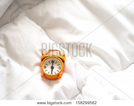 Alarm clock on bed in morning with sun light