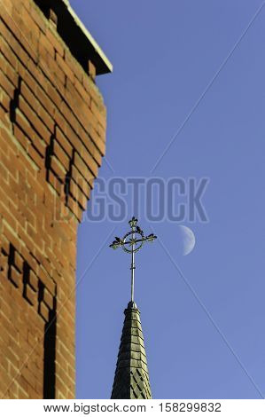 Brick chimney steeple and moon in afternoon alignment