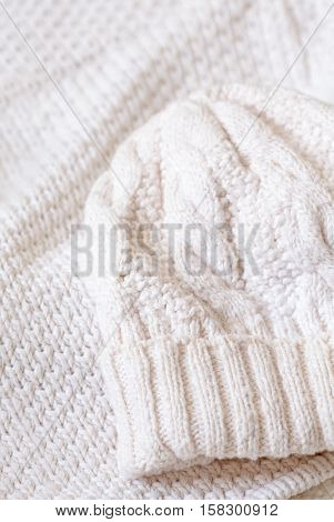 White natural clean woolen crocheted knitted sweater and hat background. Closeup