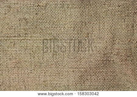 A piece of tarpaulin. The texture of coarse fabric with interwoven threads. Uneven surface. Close-up image for retro backgrounds or texturing.