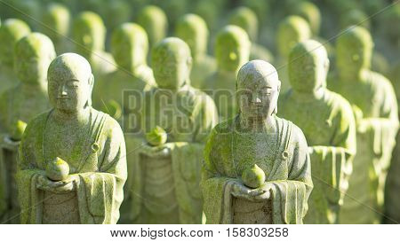 japan travel and buddha statue concept - Close up of beautiful many buddha stone statue with moss and sunlight in hasedere temple Kamamura Japan