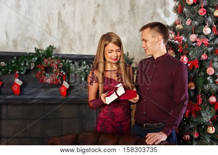 Loving couple and Christmas. She unpacks a Christmas gift from her boyfriend. In the background a beautiful Christmas tree.