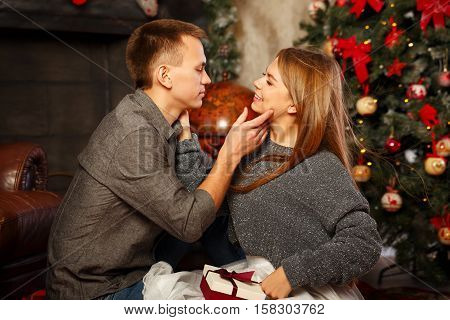 Loving couple and Christmas. Girl and boy look each other in the eye. In the background a beautiful Christmas tree.