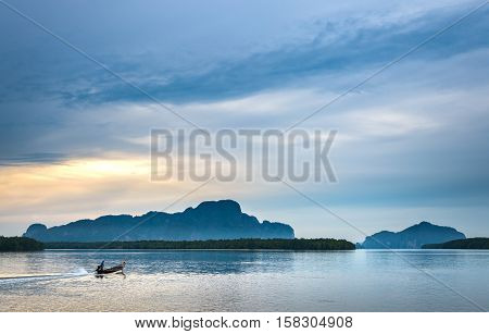 Fishermen out for fishing in every morning with longtail fishing boat at Samchong-Tai fishing village on sunrise in Phang-Nga Thailand.
