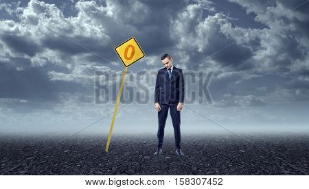 An upset businessman standing on a rocky ground in front of a yellow road sign with a zero painted on it and there are dark clouds above him. Unachieved goals. Ineffective work. Emotional pressure.