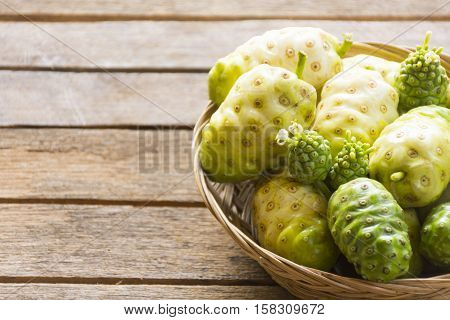 Noni fruit  in the basket on wooden table.Fruit for health and herb for health.1011
