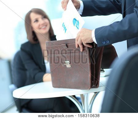 Cropped image of business woman getting documents out of briefca