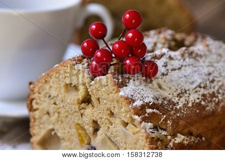 closeup of a piece of fruitcake for christmas time sprinkled with icing sugar next to a white ceramic cup with coffee or tea