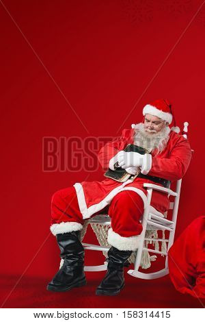 Santa Claus holding bible while napping on chair against red snowflake background