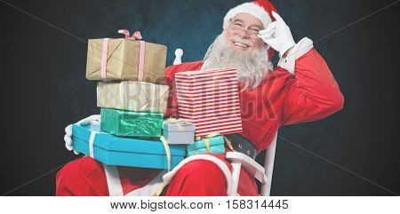 Cheerful Santa Claus holding Chritmas presents while sitting on chair against dark background