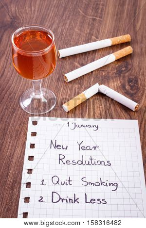 New years resolutions quit smoking and drink less written on sheet of paper and broken cigarette with glass of wine