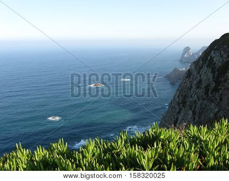 CABO DA ROCA (CAPE ROCA), PORTUGAL - OCTOBER 2014: Beautiful abandoned atlantic rocky coast with grass in foreground, westernmost extent of mainland continental Europe with clear sky in cold day.