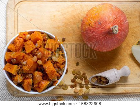 Pumpkin dessert with apple, cinnamon and raisins in white bowl on the wooden board, top view.